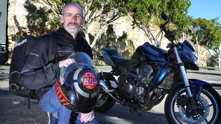 Chris Goodwin with his motorcycle which he uses to deliver Uber Eats around Sydney.