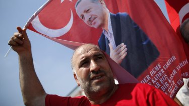 A Turkish man waves a flag, depicting the Turkish President Recep Tayyip Erdogan, during a rally in Istanbul on Sunday.