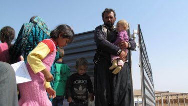 Ali Bourzan Isa holds his youngest daughter in the back of a truck that took them from the Turkish-Syrian border.