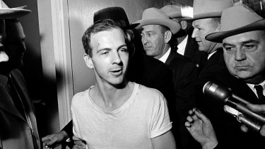 Surrounded by detectives, Lee Harvey Oswald talks to the media as he is led down a corridor of the Dallas police station.