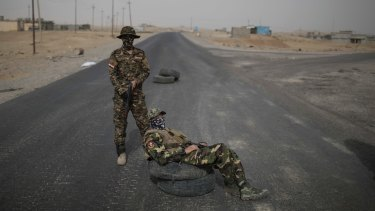 Iraqi army soldiers guard the last government-controlled checkpoint south of Mosul.