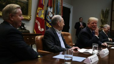 Donald Trump, right, speaks as Chuck Grassley, centre, and Lindsey Graham, left, listen during a meeting in the Roosevelt Room of the White House.