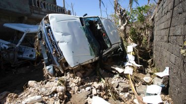 A car stands on its side after being blown away by winds brought by Hurricane Matthew in Jeremie, Haiti.