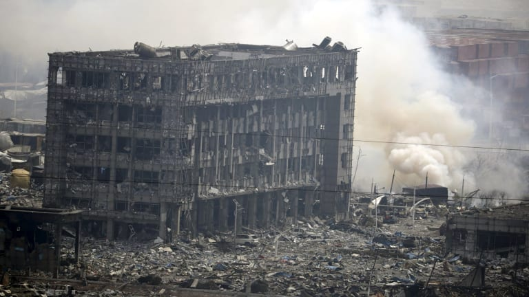 Smoke rises next to a damaged building at  the centre of the Tianjin blast.
