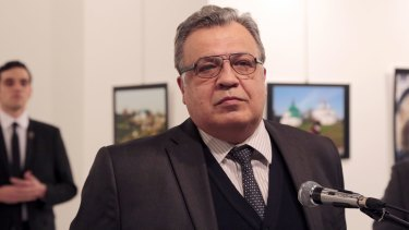 Russian Ambassador to Turkey Andrei Karlov makes an address at the gallery moments before he is shot by Mevlut Mert Altintas, seen in the background.