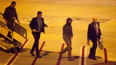 Adam Brookman arrives in Melbourne on Saturday, escorted by Australian authorities, before being extradited to Sydney.