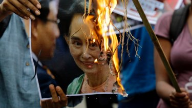 Reputation going up in flames: activists burn a poster of Aung San Suu Kyi.