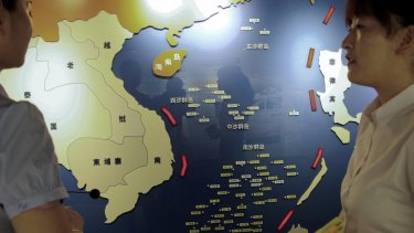 Workers chat near a map of South China Sea on display at a maritime defence educational facility in Nanjing in east China's Jiangsu province.