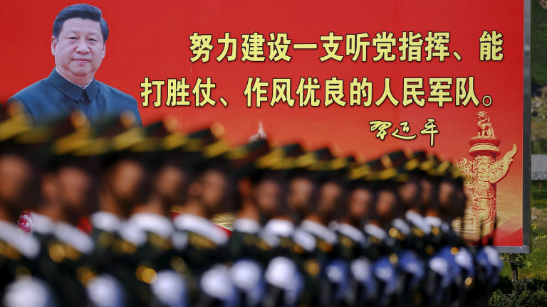 Soldiers of China's People's Liberation Army march under the gaze of a photo of President Xi Jinping.