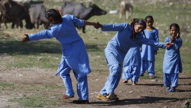 Girls play before classes at their government-run school on the outskirts of Jammu.