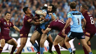 Tiger trapped: Blues prop Aaron Woods is tackled by the Queensland defence.