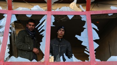In this December 28, 2015, file photo, an Afghan shopkeeper watches from the broken window of his shop near the site of suicide car bomb attack in Kabul, Afghanistan.
