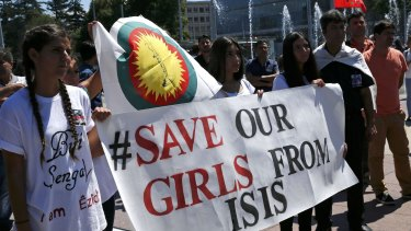 Women hold a banner at a demonstration on Monday at the UN European headquarters in Geneva, Switzerland, marking the first anniversary of Islamic State's surge on Yazidis of the town of Sinjar.