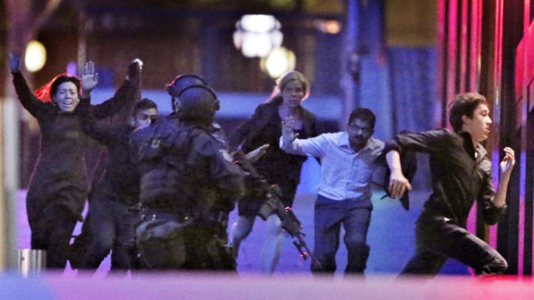 Hostages flee from the Lindt cafe in Martin Place during the early hours of December 16, 2014.
