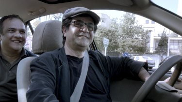 Jafar Panahi and a passenger in <i>Tehran Taxi</i>, a minimalist experiment where fiction and documentary mingle.
