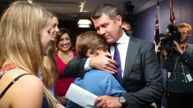 Premier Mike Baird embraces his family after Thursday's press conference where he announced his resignation.