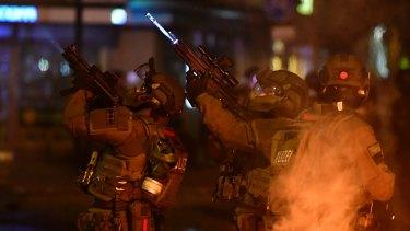A SWAT team hold machine guns while observing an apartment during an anti-G20 protest.
