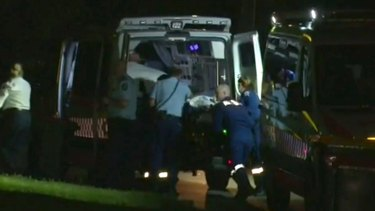 A 56-year-old man is loaded into an ambulance after being stabbed in Moorebank.