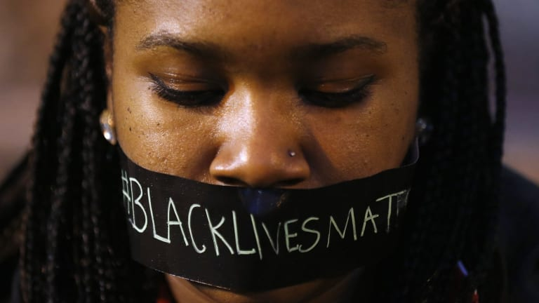 A protester wears tape over her mouth during a silent demonstration against what they say is police brutality after the Ferguson shooting of Michael Brown.