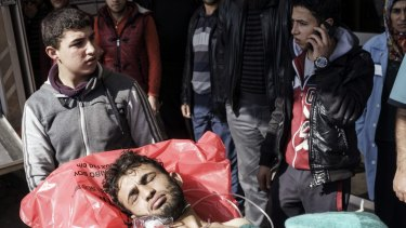 A wounded Syrian man is carried to a hospital in Kilis, Turkey. An air strike in the northern Syrian province of Idlib destroyed a makeshift clinic supported by an international aid group on Monday.