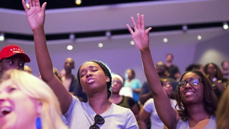 Allyson LaFrance and Amber Shields (right) raise their hands during a service at Concord Church in Dallas.