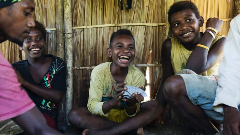 Children play card games in the province of Guadalcanal.