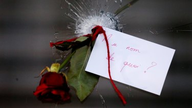 """A rose in a bullet hole with a note that translates to """"In the name of what?"""" at La Belle Equipe in Paris France on Sunday 15 November 2015."""