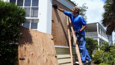 David Montes helps board windows at a home in preparation for Hurricane Harvey in Corpus Christi, Texas.