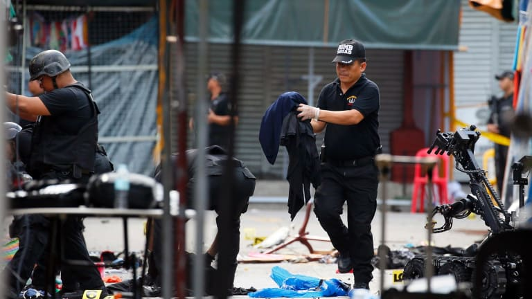 Members of the Philippine National Police Bomb Squad remove items following two explosions in Manila's Quiapo district.