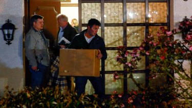 German police carry boxes out of a house believed to belong to the parents of Andreas Lubitz on Thursday.