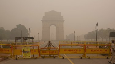 A Delhi policeman stands guard at the closed war memorial, which is engulfed in a thick smog.