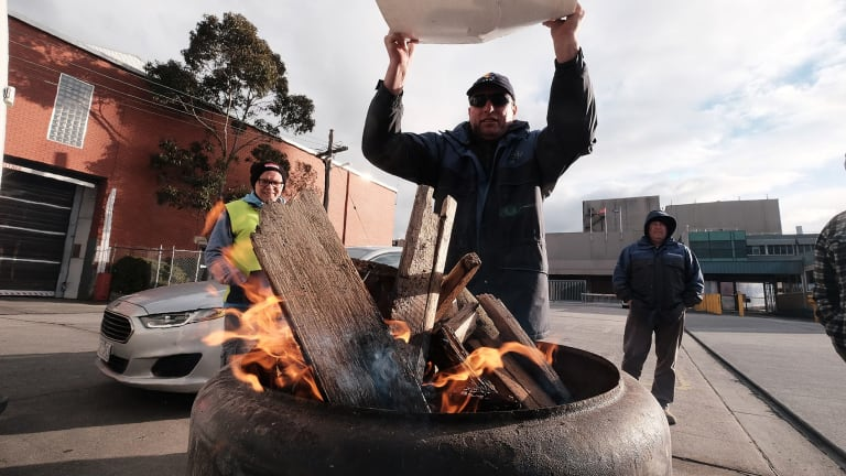 Sacked workers try to keep warm on the picket line.