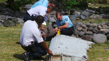 French police inspect the flaperon, now confirmed to be from MH370, on Reunion Island.