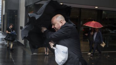 Commuters toil with Sydney's inclement weather.