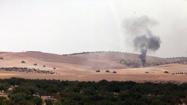 Turkish army tanks move toward the Syrian border as pictured from Karkamis, Turkey.