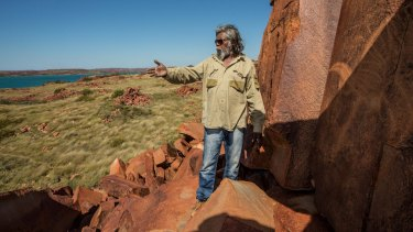 Senior cultural ranger at Murujuga National Park, Jakari Togo, looks out to sea next to rock carvings on the Burrup Peninsula.