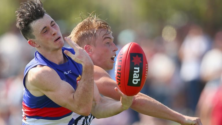 Toby McLean of the Bulldogs and Bernie Vince compete for a mark.