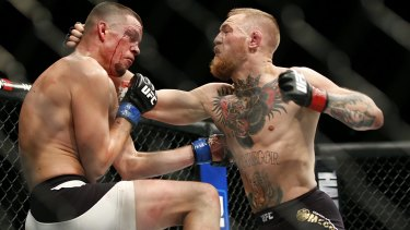 Conor McGregor, right, trades punches with Nate Diaz during his losing UFC 196 welterweight mixed martial arts match in Las Vegas.