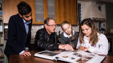 Holocaust survivor Peter Halas shows (L-R) Alex Tofler, Lily Shrire and Zoe Menczel Shrire a photo album of his family that were affected by the holocaust.