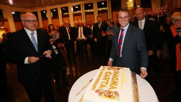 Attorney-General Senator George Brandis and Human Rights Commissioner Tim Wilson celebrate the 800th anniversary of Magna Carta with cake at Parliament House in 2015.