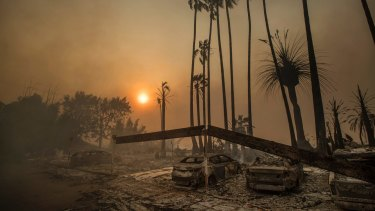Smoke rises behind a leveled apartment complex as a wildfire burns in Ventura, California.