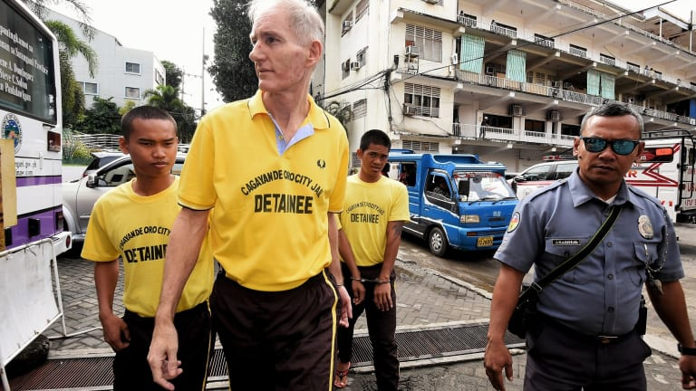 Peter Scully (second from left) arrives at the Cagayan De Oro court handcuffed to another inmate on the first day of his trial in September.