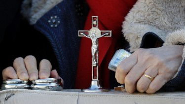 A woman holds her holy items as she attends Pope Francis' weekly general audience, in St. Peter's Square, at the Vatican.
