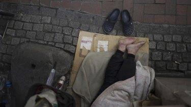 A homeless man rests under a pedestrian bridge.