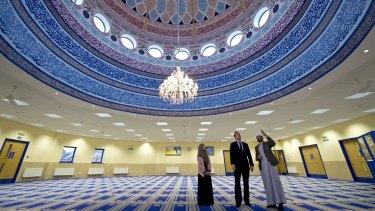 Prime Minister David Cameron talks with Imam Qari Asim (R) and Shabana Muneer, a member of Makkah Masjid mosque's women's group, as he visits Makkah Masjid Mosque in Leeds, England.