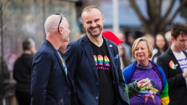 ACT Chief Minister Andrew Barr (with partner Anthony Toms) in one of the new CBR T-shirts.