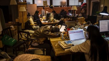 Employees of start ups work at their desks at You+ in Beijing.