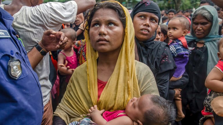 Rohingya Muslim women, who crossed over from Myanmar into Bangladesh, wait to receive aid near Balukhali refugee camp.