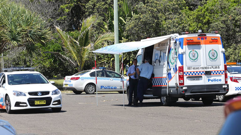 Police vehicles at Shelly Beach on Monday after a surfer was killed by a shark.
