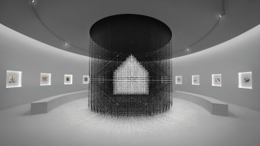 An impression of the nendo 'chandelier' of 30,000 tiny houses surrounded by Escher prints.